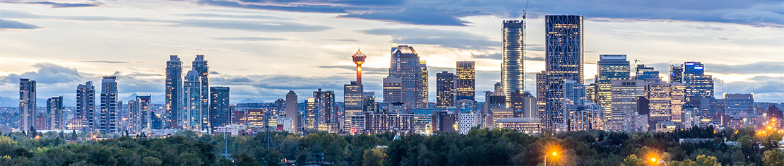 Downtown Calgary at dusk with city lights.